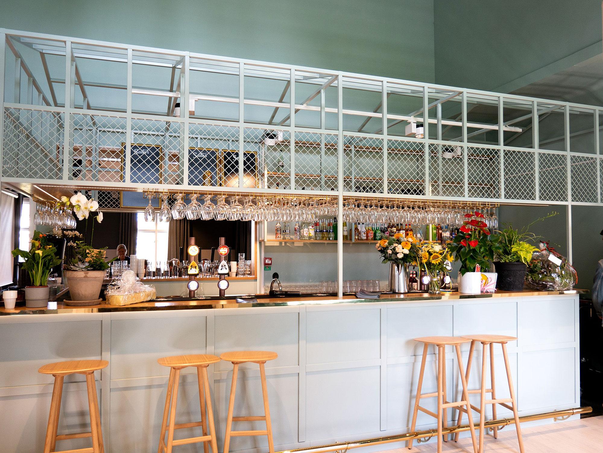 En vit bardisk med ljusgröna väggar, barstolar i trä, glas som hänger upp och ned, ölappar och blommor som dekoration.