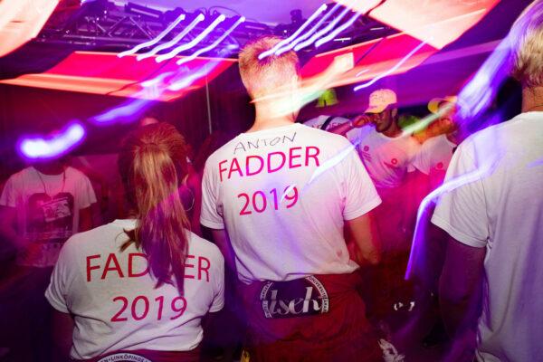 Bild på två person i fadder t-shirtar i klubb med neonljus
