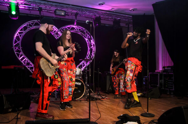 Studenter som uppträder på scen i ett band i röda overaller