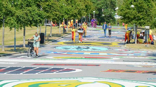 Bild på studenter so promenerar över färgglad mark